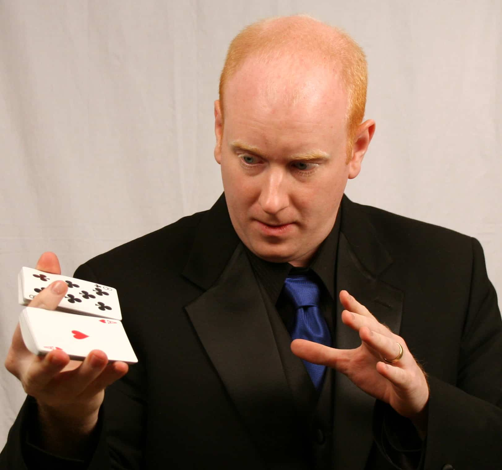 Magic Scott portrait shuffling a deck of cards with one hand.